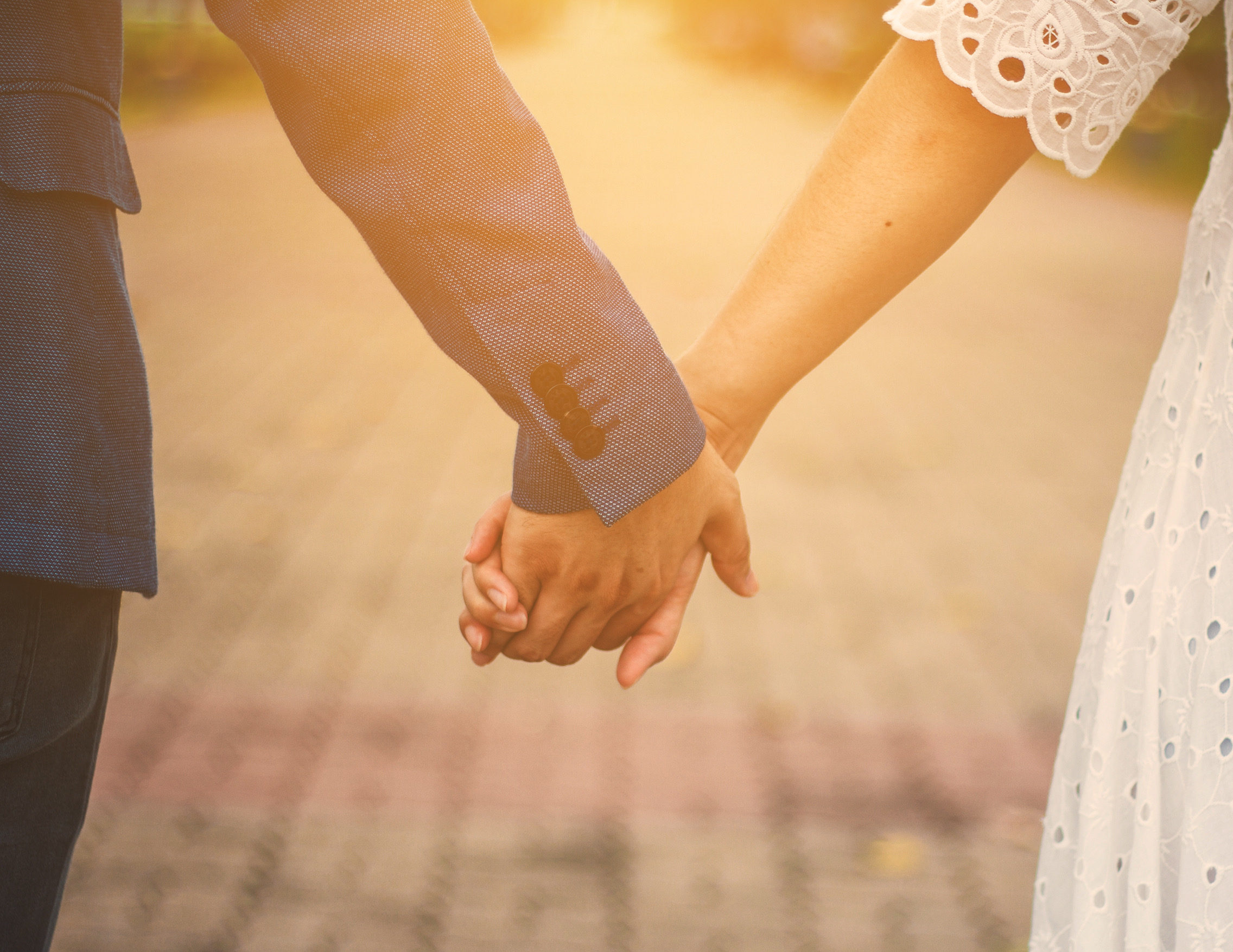 couple holding hands with sunlight  in park